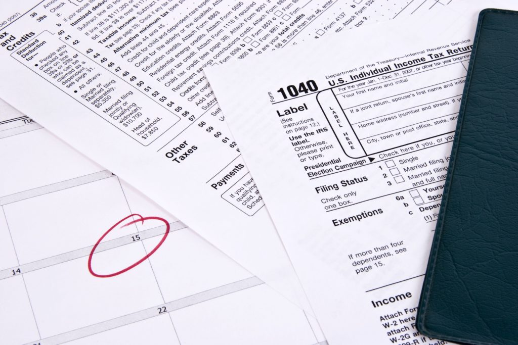 Picture of income tax documents and a calendar with the 15th of the month circled.